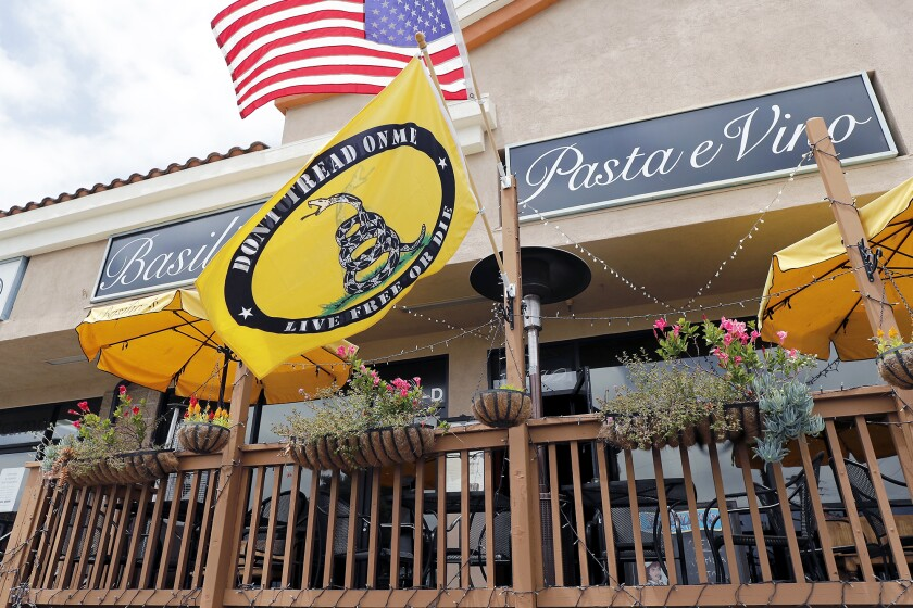 A Gadsden flag is hung with the flag of the United States of America at Basilico's Pasta e Vino in Huntington Beach.