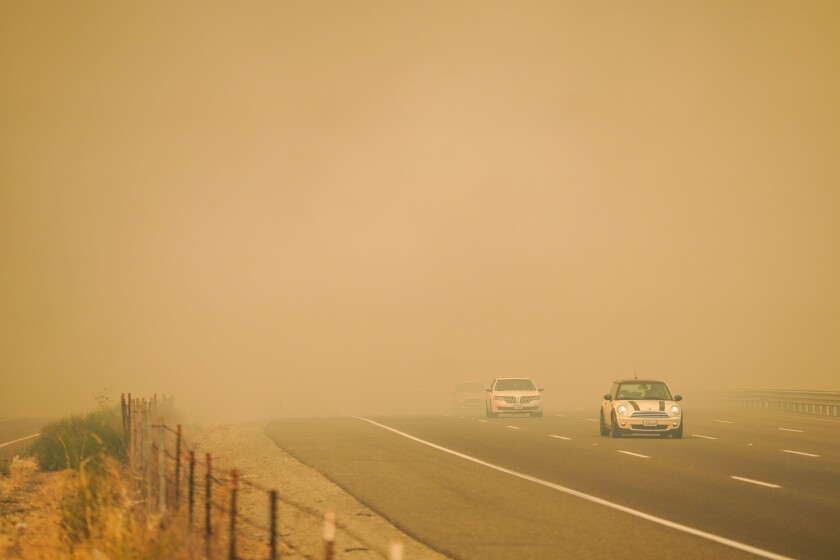 Cars drive through smoke that blankets the Dwight D. Eisenhower Highway as firefighters battle blazes in Vacaville, Calif.