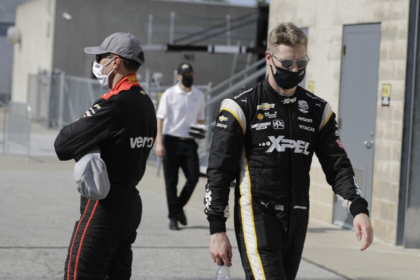 Josef Newgarden, right, walks past Will Power, of Australia, after Power won the pole for the IndyCar auto race at Indianapolis Motor Speedway in Indianapolis, Friday, July 3, 2020. (AP Photo/Darron Cummings)