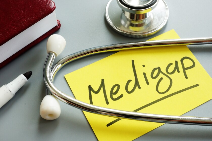 This photo shows a piece of paper with the word Medigap on it. A stethoscope lies over the note.