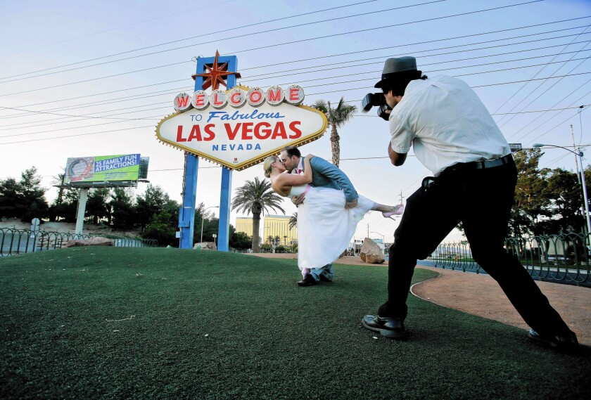 Katy Garrett and husband Stuart strike a pose near a Vegas welcome sign in 2012. Las Vegas' Marriage License Bureau has reopened.