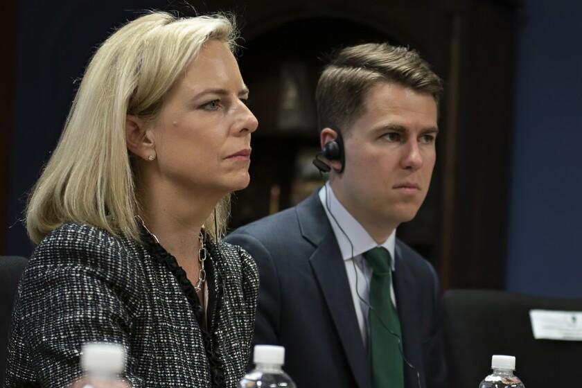 """This March 27, 2018, provided by the Department of Homeland Security, then-Secretary of Homeland Security Kirstjen Nielsen and then-Department of Homeland Security chief of staff Miles Taylor, right, meet with Honduran President Juan Hernandez, not pictured, and security ministers from the Northern Triangle countries in Tegucigalpa, Honduras. Taylor, a former Trump administration official who penned a scathing anti-Trump op-ed and book under the pen name """"Anonymous"""" made his identify public Wednesday, Oct. 28, 2020. (Tim Godbee/Department of Homeland Security via AP)"""