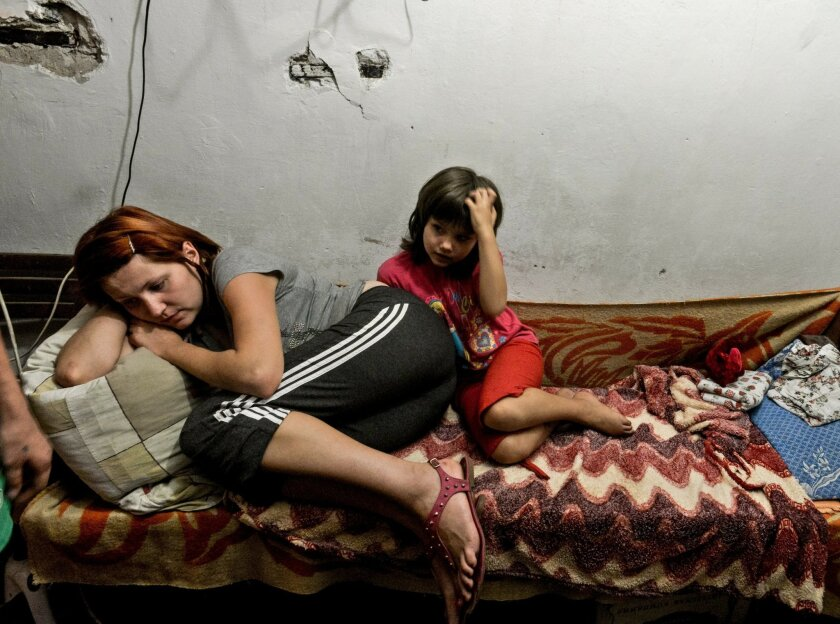 A mother and child lie on the bed in the bomb shelter in Petrovskiy district, in Donetsk, eastern Ukraine, Monday Sept. 1, 2014. The Petrovskiy district of Donetsk is currently a frontline and one of the districts which has suffered the most from the artillery fights between Ukrainian army and Pro-Pussian rebels. (AP Photo/Mstislav Chernov)