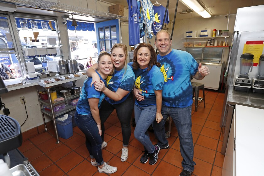 Sugar 'n Spice owners Courtney and Will Alovis, right, pose with employees Fiona and Eilish Zachary as the business celebrates 75 years on Balboa Island in Newport Beach.