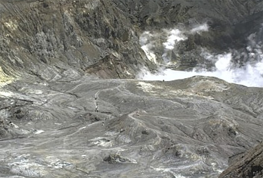 In this image released by GeoNet, tourists can be seen on a trail near the volcano's crater Monday, Dec. 9, 2019, on White Island, New Zealand. Prime Minister Jacinda Ardern says about 100 tourists were on or near White Island when the volcano erupted and some of them are missing. (GNS Science via AP)