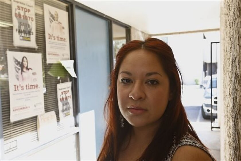 Reyna Avila, who recently received a work permit and Social Security card under new Obama administration policy for young immigrants, is shown here at her place of work Tuesday, April 2, 2013, in Phoenix. President Barack Obama's decision last year to allow young people living in the U.S. illegally