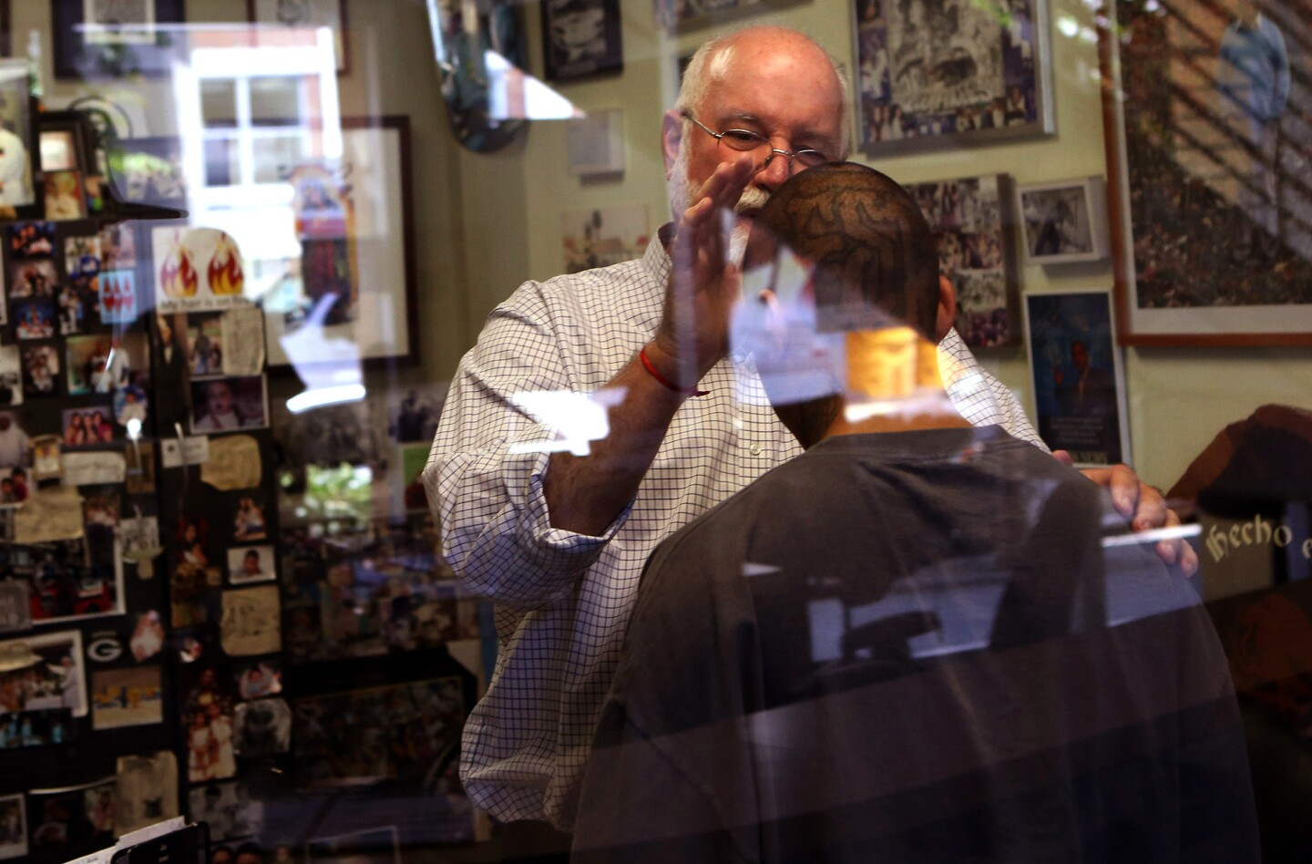 Father Gregory Boyle, founder and director of Homeboy Industries, prays over Rolando Motta, 26, in his office. Boyle created Homeboy Industries to assist high-risk youth.