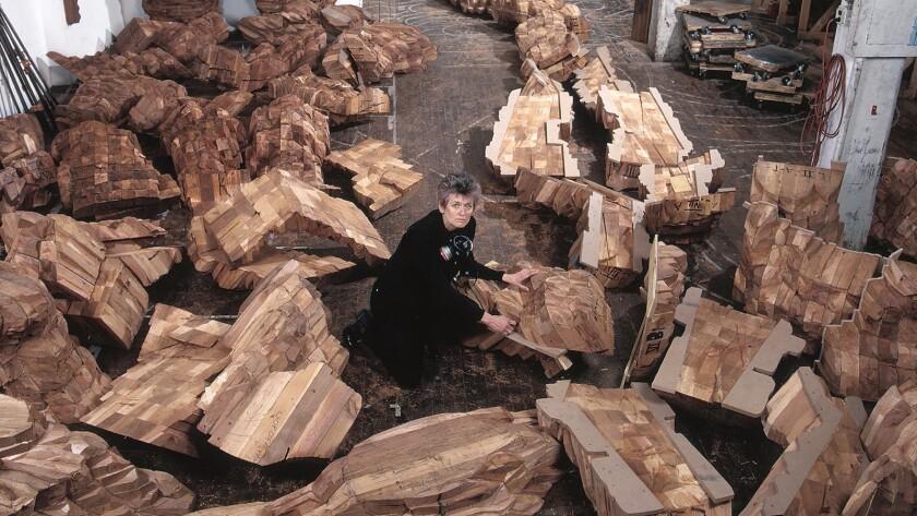 "Ursula von Rydingsvard in her Williamsburg studio in 2002 with cedar casts of ""Katul Katul."""