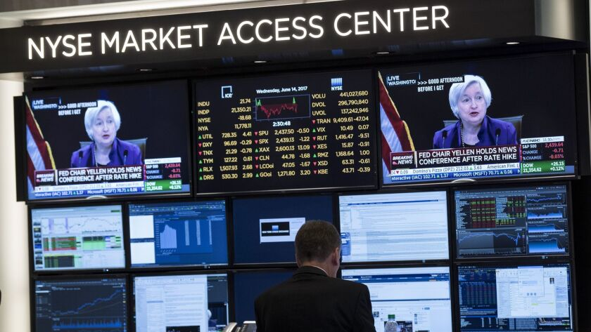 Traders work on the floor of the New York Stock Exchange as a television monitor displays Federal Reserve Chairwoman Janet Yellen announcing the Fed's decision to raise interest rates on June 14.