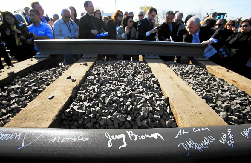 Invited guests sign segments of railroad track during a groundbreaking ceremony for a bullet train station in Fresno on Tuesday.