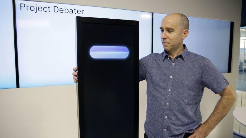IBM's Project Debater artificial intelligence machine stands alongside Noam Slonim, the project's progenitor, in 2018.