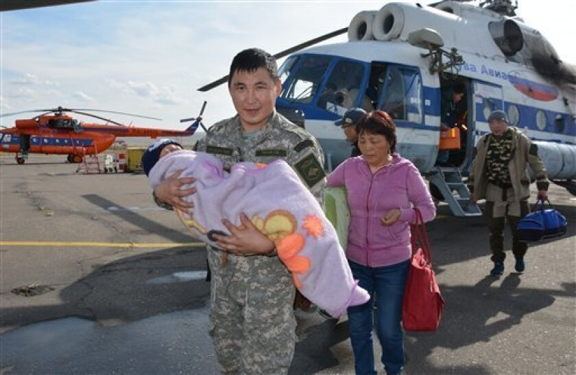 En esta fotografía del miércoles 21 de septiembre de 2016, facilitada por el Ministerio de Manejo de Emergencias de Tuva, Rusia, un soldado carga un niño que pasó tres días perdido en un bosque siberiano.