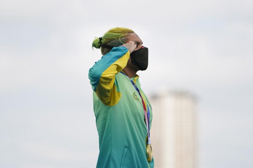 La medallista de oro, la brasileña Ana Marcela Cunha. saluda mientras se entona el himno nacional durante la ceremonia de premiación, el miércoles 4 de agosto de 2021, en Tokio. (AP Foto/Jae C. Hong)