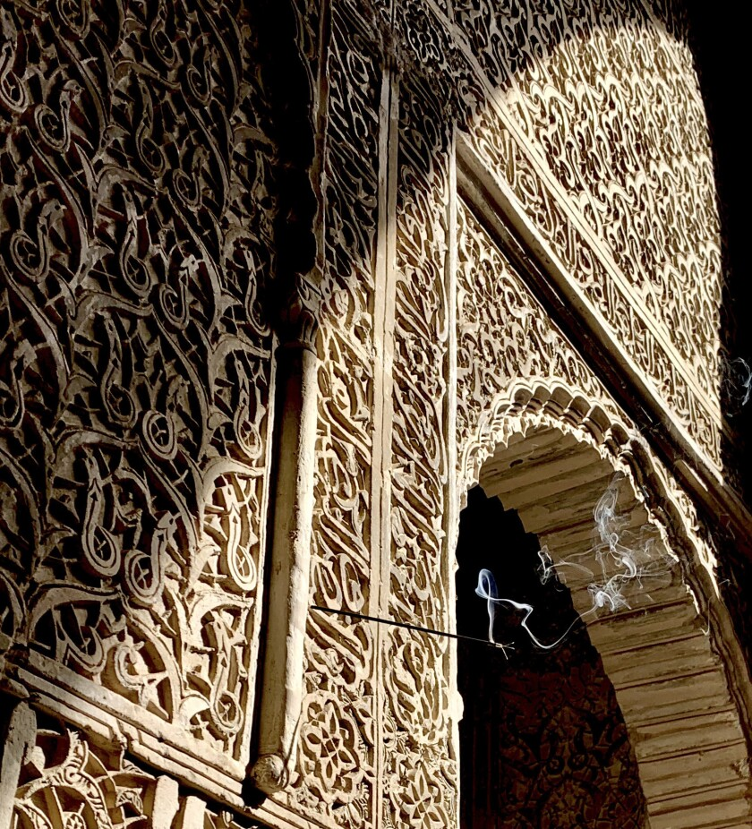 FEZ, MOROCCO - A stick of incense burns from one of the sumptuously decorated stucco walls at Bou In