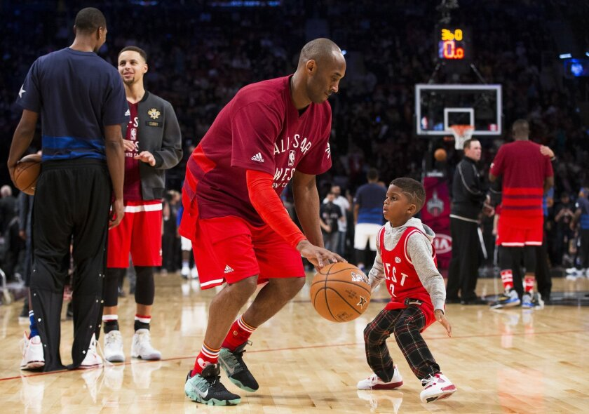 Western Conference's Kobe Bryant, of the Los Angeles Lakers, (24) plays around with Los Angeles Clippers' Chris Paul's son Chris Paul Jr. during second half NBA All-Star Game basketball action in Toronto on Sunday, Feb. 14, 2016. (Mark Blinch/The Canadian Press via AP) MANDATORY CREDIT