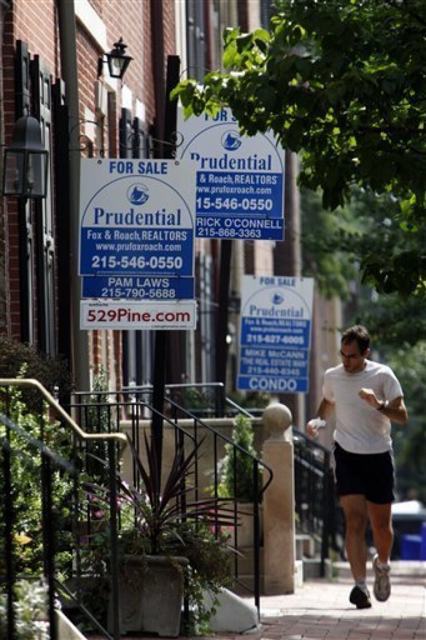 A person runs past three for sale signs posted on homes in Philadelphia, Friday, Aug. 21, 2009. Home resales posted the largest monthly increase in at least 10 years last month as first-time buyers rushed to take advantage of a tax credit that expires this fall. (AP Photo/Matt Rourke)