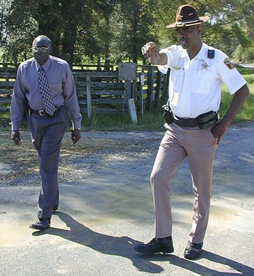 """In this March 21, 2000 photo, Lowndes County Sheriff Willie Vaughner, left, and chief deputy John Williams stand at the intersection where Williams apprehended Jamil Abdullah Al-Amin on Monday evening in White Hall, Ala. Williams was fatally shot in the line of duty Saturday evening, Nov. 23, 2019, in a county near the state capital city, Alabama Gov. Kay Ivey said. Ivey tweeted that Lowndes County Sheriff Williams was """"a pillar of the community."""" (Al Benn/Montgomery Advertiser via AP)"""