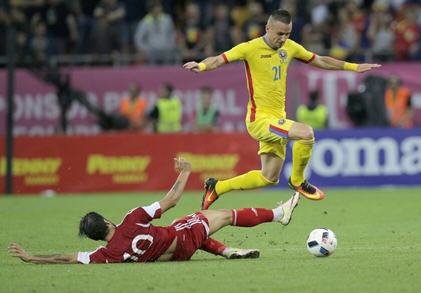 Romania's Dragos Grigori, right, vies for the ball with Georgia's Tornike Okriashvili, left, during the international friendly soccer match between Romania and Georgia on the National Arena stadium, in Bucharest, Romania, on Friday, June 3, 2016. (AP Photo/Vadim Ghirda)