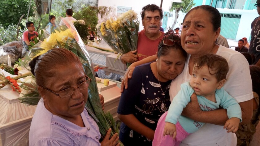 Facunda Villanueva Perez, 67, whose sister was among the 11 killed at the Atzala church in Mexico, holds her grandchild and mourns with relatives at the victims' wake Wednesday.