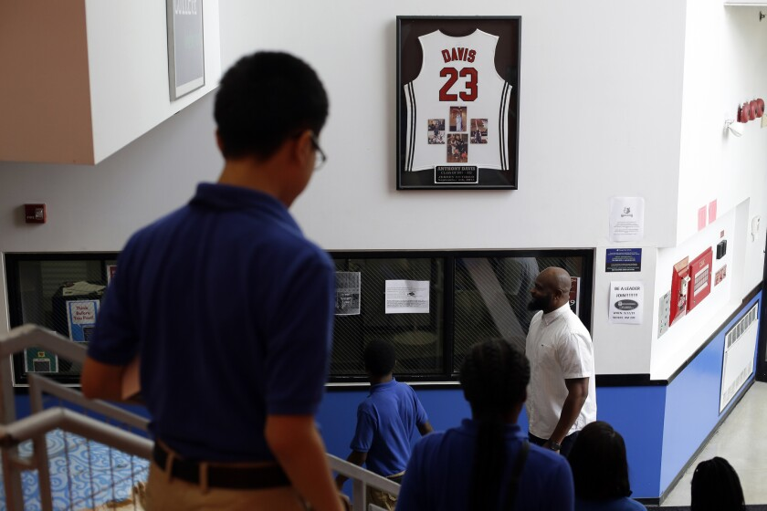 Tiray Jackson of Perspectives Charter Schools stands under the Anthony Davis's jersey.