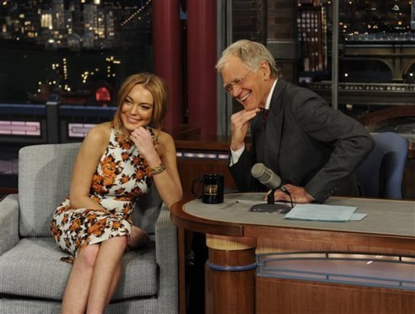 """In this Tuesday, April 9, 2013 photo released by CBS Entertainment, actress Lindsay Lohan talks to David Letterman about her upcoming trip to rehab, her guest star roles in the series """"Anger Management"""" and film """"Scary Movie 5"""" and more during the """"Late Show with David Letterman,"""" (11:35 PM-12:37 AM, ET/PT) on the CBS Television Network, in New York. (AP Photo/CBS Entertainment, Jeffrey R. Staab)"""