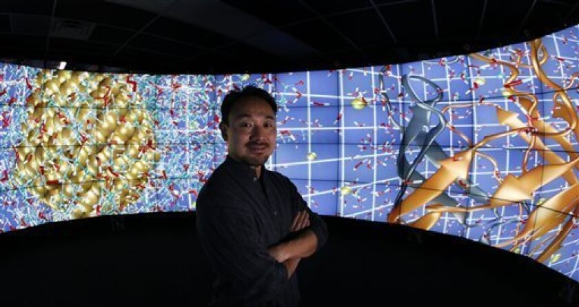 In this photo made Thursday, Jan. 24, 2013, in Chicago, University of Illinois-Chicago computer scientist Jason Leigh, co-inventor of the CAVE2 virtual reality system, stands in the CAVE2 where the system's 72 stereoscopic liquid crystal display panels encircles the viewer 320 degrees and creates