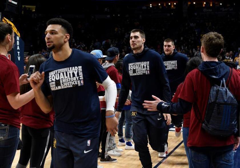 El jugador Jamal Murray (i), Juancho Hernangomez (c) y Nikola Jokic (d) de Denver Nuggets entran a la cancha durante un juego de la NBA. EFE/Archivo