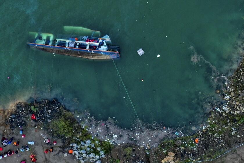 En esta foto publicada por la Agencia de Noticias Xinhua, de un barco de pasajeros volcado en Liupanshui, en la provincia de Guizhou, suroeste de China, el domingo 19 de septiembre de 2021. (O Dongqu/Xinhua vía AP)