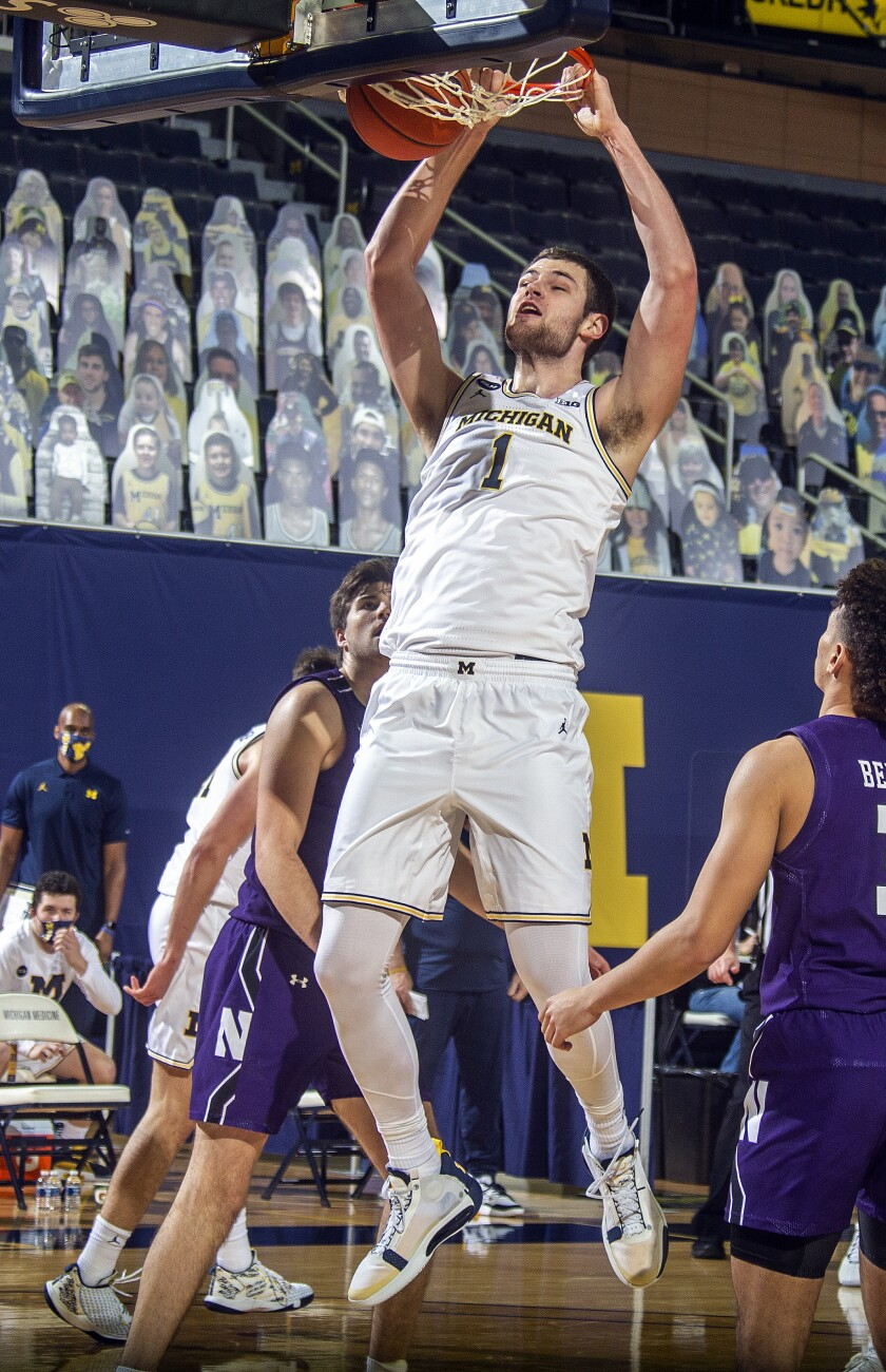 Michigan center Hunter Dickinson (1) dunks in the second half of an NCAA college basketball game against Northwestern at Crisler Center in Ann Arbor, Mich., Sunday, Jan. 3, 2021. (AP Photo/Tony Ding)