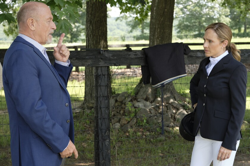 A man in a suit talks to a woman in riding gear.