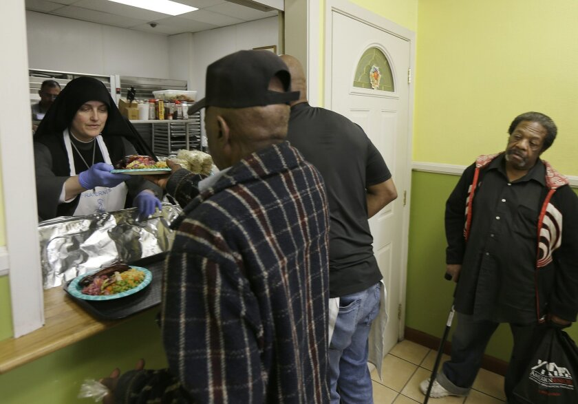 Sister Mary Benedicte, left, serves food at the Fraternite Notre Dame Mary of Nazareth Soup Kitchen in San Francisco, Tuesday, Feb. 9, 2016. SanFrancisco nuns who serve the homeless are in danger of getting kicked out of their home after a rent hike of more than 50 percent. (AP Photo/Jeff Chiu)