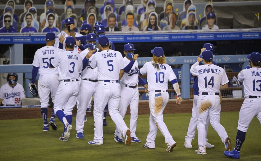Dodgers players are congratulated by masked members of the coaching staff after a win over the San Francisco Giants