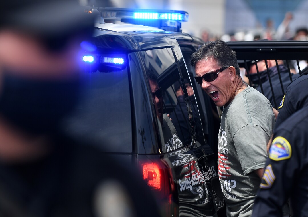 A man in sunglasses is ushered into the back of a police vehicle