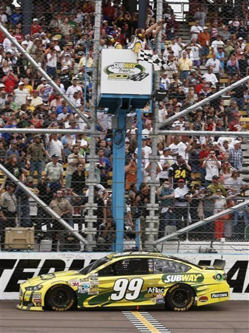 FILE - In this March 3, 2013, file photo, driver Carl Edwards takes the checkered flag to win the NASCAR Sprint Cup Series auto race in Avondale, Ariz. Jimmie Johnson didn't like the way Edwards restarted the race at Phoenix, intimating Edwards didn't follow the rules to the letter while snapping h