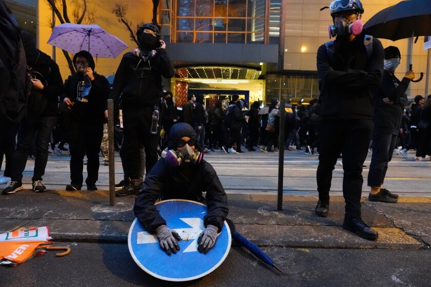 A group of protestors take rest as others march behind in Hong Kong, Wednesday, Jan. 1, 2020. Hong Kong toned down its New Year's celebrations amid the protests that began in June and which have dealt severe blows to the city's retail, tourism and nightlife sectors. (AP Photo/Vincent Yu)