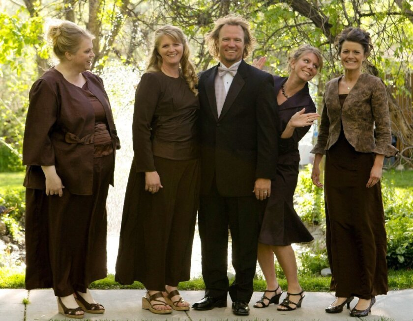 """Kody Brown poses with his wives in a promotional photo for TLC's reality TV show, """"Sister Wives."""" Advocacy groups for polygamy and individual liberties hailed a federal judge's ruling last week that key parts of Utah's polygamy laws are unconstitutional."""