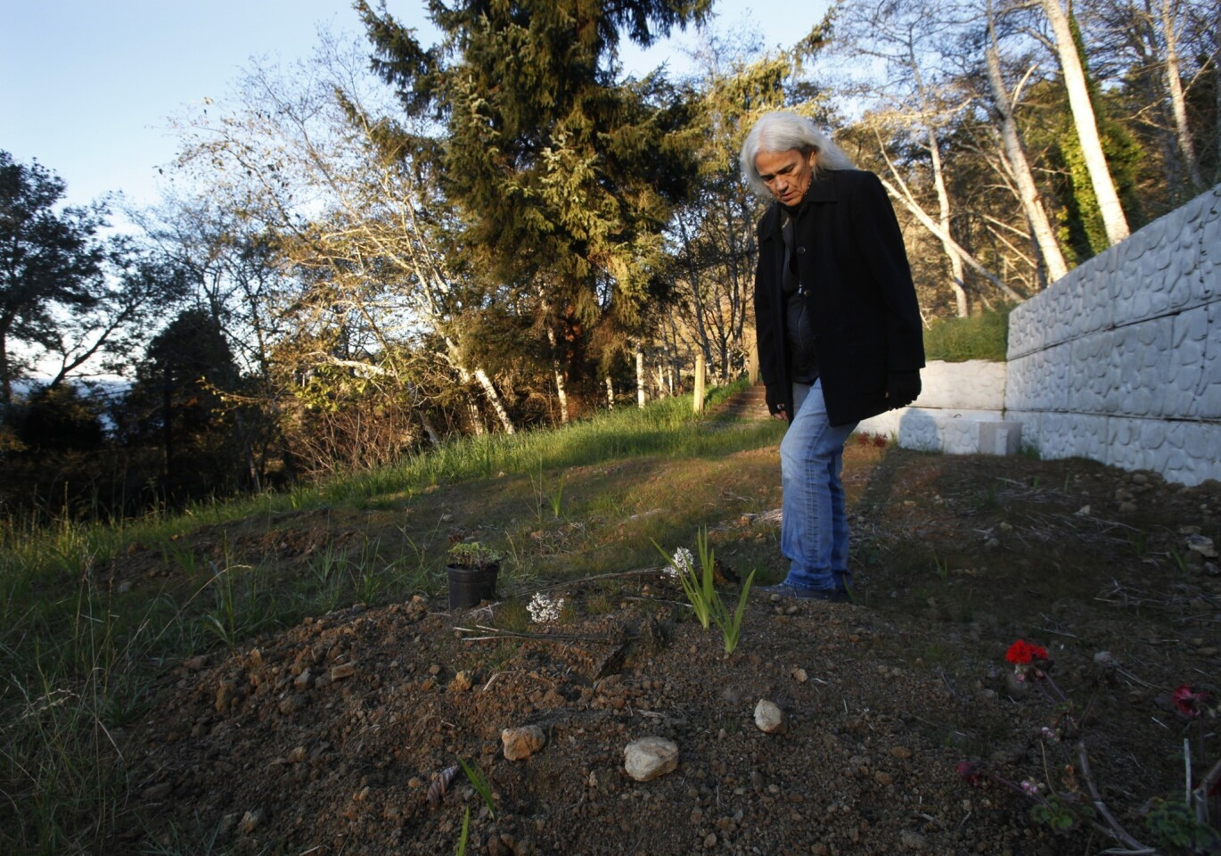 As the sun rises, Abinanti places flowers on her mother's grave next to her home at the mouth of the Klamath River along California's north coast. Abinanti visits the grave, now on her tribal land, before going to work.