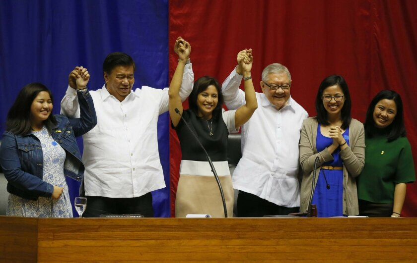 "Congresswoman Leni Robredo is proclaimed Philippine Vice-president-elect by Senate President Franklin Drilon, second from left, and House Speaker Feliciano Belmonte, third from right, during a ceremony Monday, May 30, 2016 at the Lower House in suburban Quezon city northeast of Manila, Philippines. Robredo won over her closest rival Sen. Ferdinand ""Bongbong"" Marcos Jr., the son of the late strongman Ferdinand Marcos who ruled the country for 20 years. (AP Photo/Bullit Marquez)"