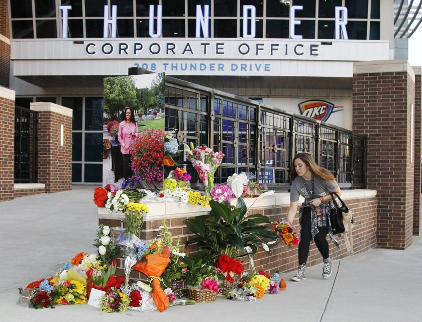 Rebekah Murphy drops off flowers at a memorial for Ingrid Williams, the wife of Thunder assistant coach Monty Williams, who died Wednesday as the result of a car accident Tuesday, before an NBA basketball game between the New Orleans Pelicans and the Oklahoma City Thunder in Oklahoma City, Thursday