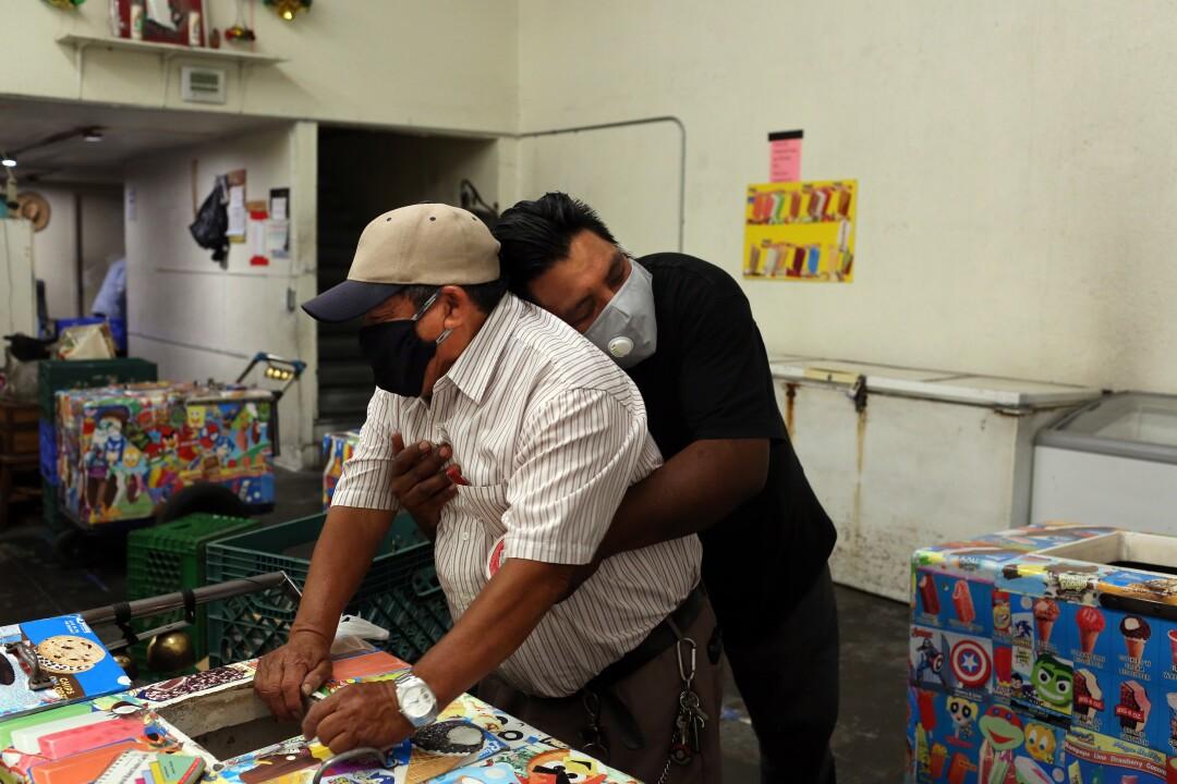 Oscar Samano, right, hugs Rios inside Barahona Ice Cream.
