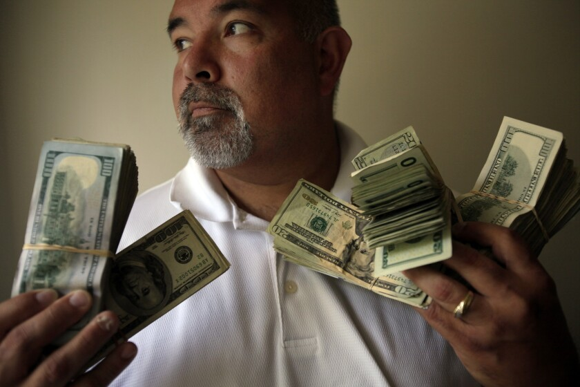 Butch Gupta, an investigator with the Mendocino County district attorney's office, holds about $45,000 in seized cash.