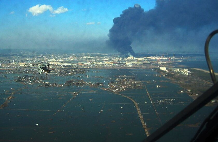 """THe Navy says, """"An SH-60B helicopter assigned to the Chargers of Helicopter Antisubmarine Squadron (HS) 14 from Naval Air Facility Atsugi flies over the port of Sendai to deliver more than 1,500 pounds of food to survivors of an 9.0 magnitude earthquake and a tsunami. The citizens of Ebina City, Ja"""