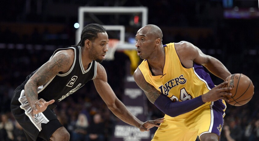 Kobe Bryant, right, controls the ball in front of Kawhi Leonard during a game between the Lakers and San Antonio Spurs in January 2016.