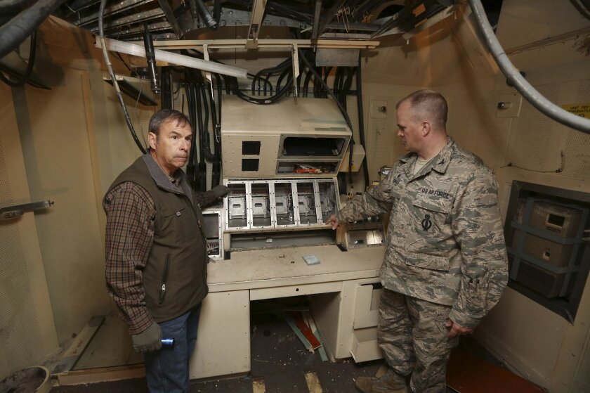FILE - In this April 6, 2015 file photo, retired Air Force Col. Barry Kistler, left, and Col. Todd Sauls stand at a former control panel  in the underground launch control center at the Air Force's Quebec-01 Missile Alert Facility north of Cheyenne, Wyo. The Air Force has been restoring the missile