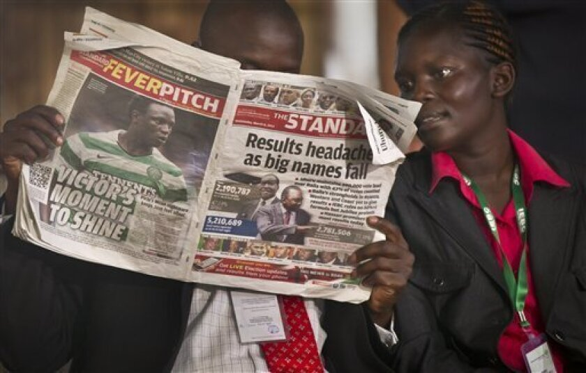 An election official reads a copy of The Standard newspaper while waiting for election results to be announced at the National Tallying Center, in Nairobi, Kenya Thursday, March 7, 2013. Kenyan media members told The Associated Press on Thursday that the Media Owners Association agreed not to sensa