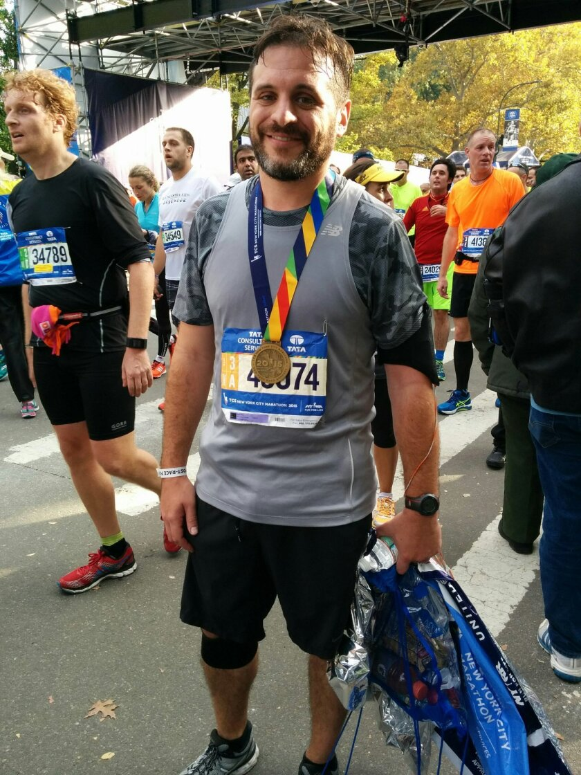New York Mets assistant clubhouse manager Dave Berni poses for a photo after completing the New York City Marathon, Sunday, Nov. 1, 2015, in New York. Berni sandwiched running the marathon between Games 4 and 5 of the World Series. (AP Photo/Julie Walker)