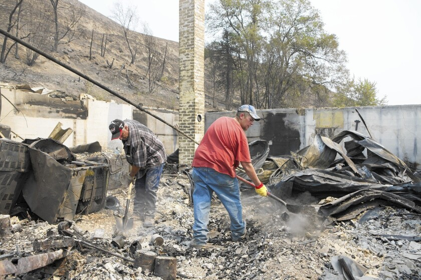 Rich Pitkethly left, and Randy Loucks, both of Brewster, Wash., dig through the remains of the Pateros, Wash., house of Loucks' mother-in-law, one of more than 150 homes destroyed by the Carlton Complex fire.