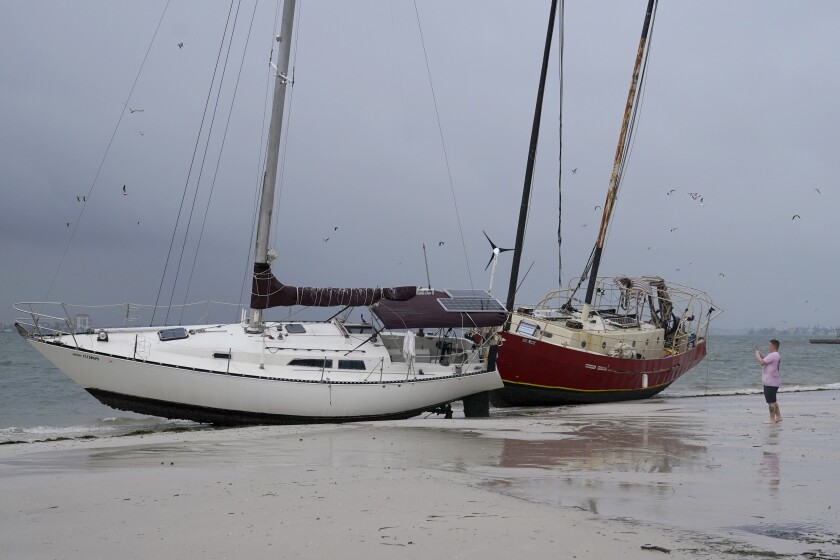 Boats sit on the beach in the aftermath of Tropical Storm Eta on Thursday in Gulfport, Fla.