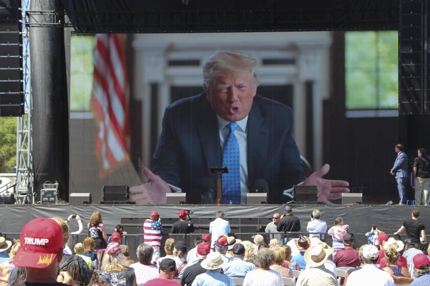 رئیس جمهور سابق ترامپ روی صفحه بزرگی که چندین نفر آن را تماشا می کنند ، پیش بینی کرده است.