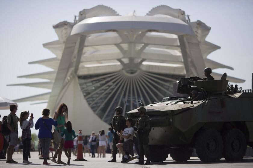 Personas se toman fotos con militares en un vehículo blindado que patrulla el Museo del Mañana en Río de Janeiro el sábado, 9 de julio de 2016, en Río. (AP Photo/Leo Correa)